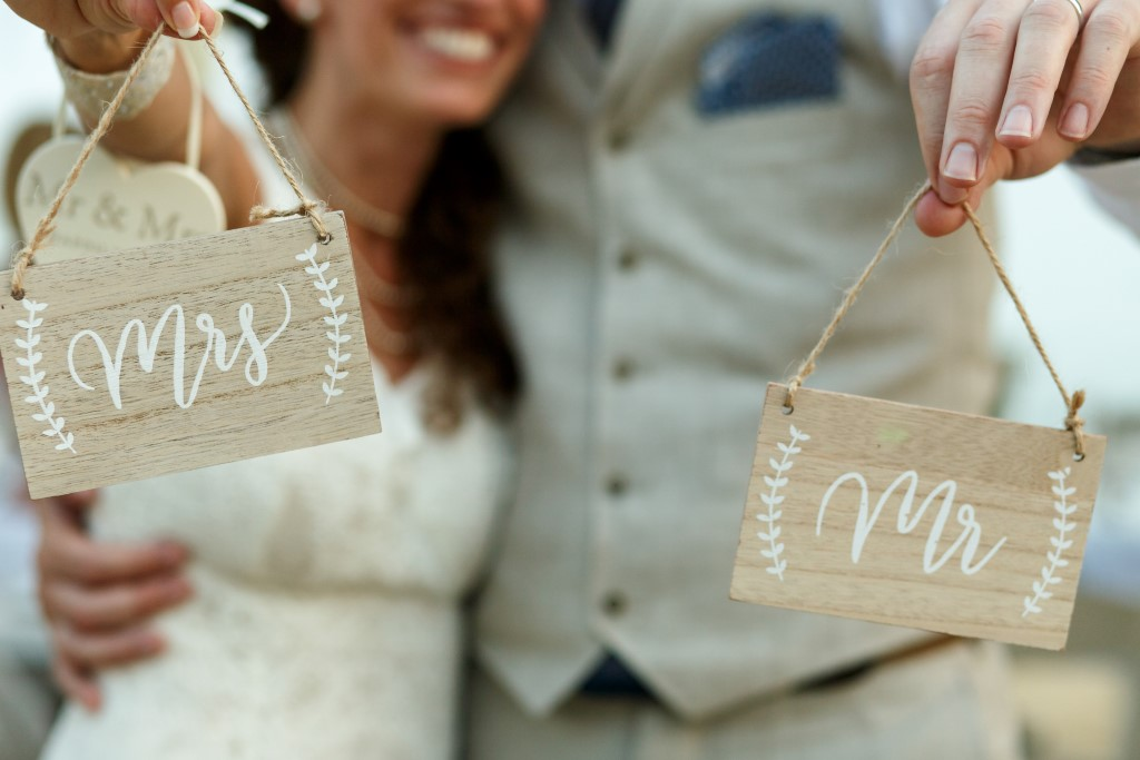 Happy newlyweds hold wooden boards with letterings 'Mrs' and 'Mr